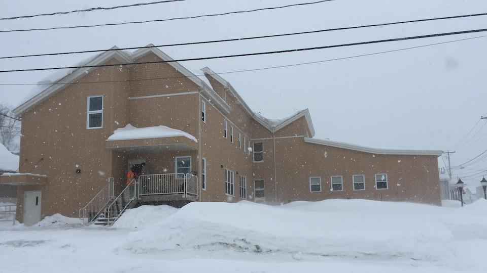 Un immeuble comprenant plusieurs chambres vu de l'autre côté de la rue, en hiver.