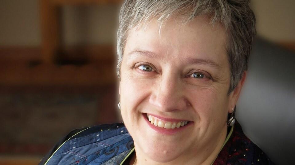 La révérende Anne Barker assise à son bureau.