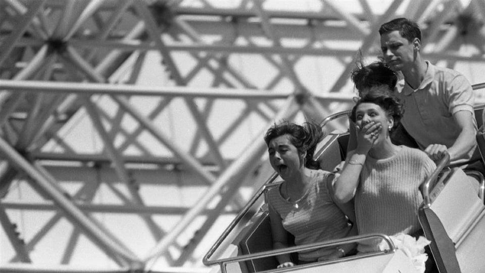 Quatre personnes prennent place dans un wagon d'un manège du parc d'attractions La Ronde, à Montréal.