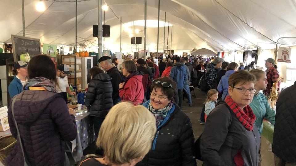 Des dizaines de personnes circulent sous un chapiteau où des gens vendent leurs produits.