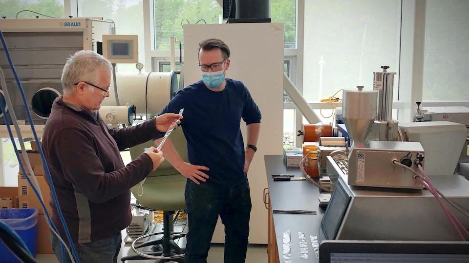 Les deux hommes dans le laboratoire, dont l'un porte un masque médical, examinent une bandelette de plastique.