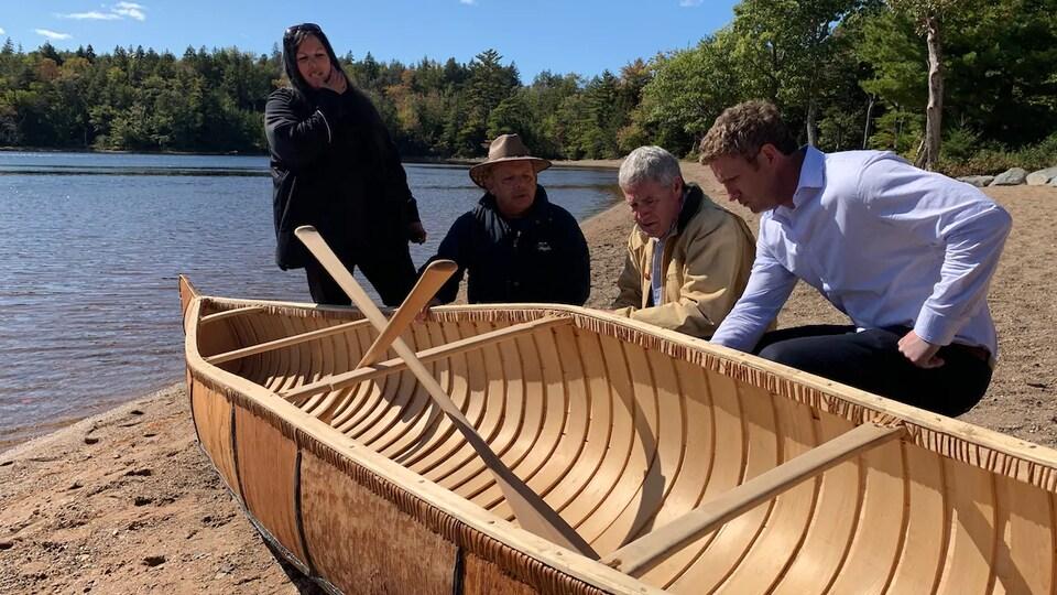 Les quatre personnes contemplent le canot sur la berge d'un lac.