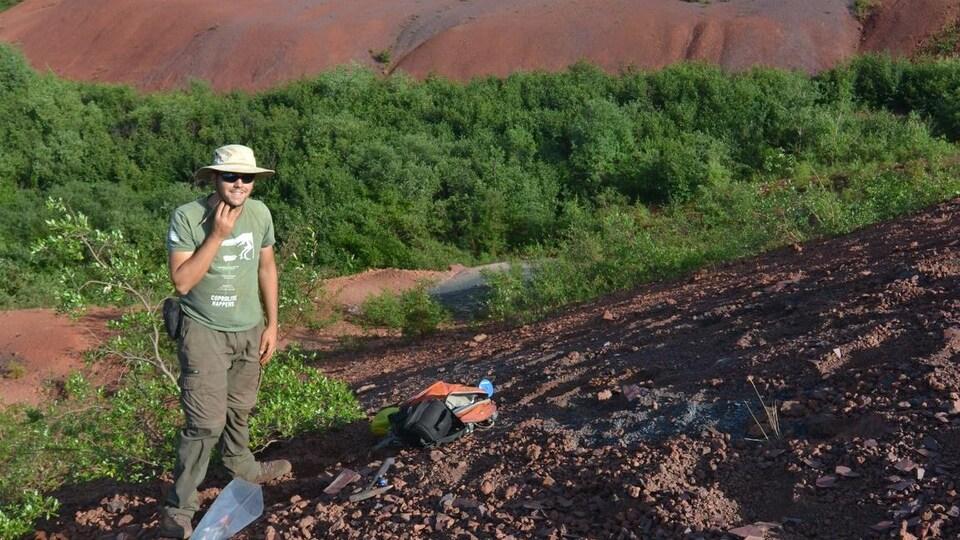 Un homme sur un mont de roches. En arrière-plan des arbustes et un lac.