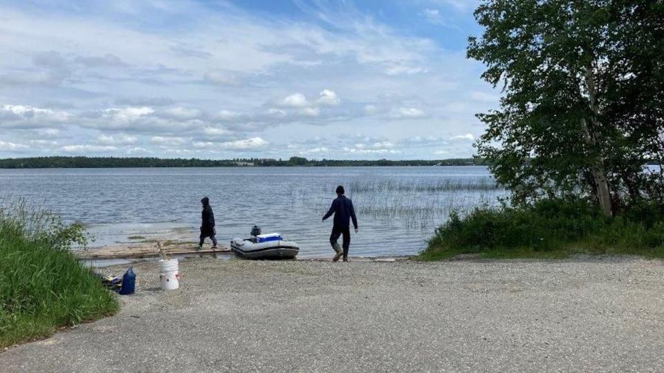 Des personnes sur la rive d'un lac avec une chaloupe gonflable accostée au bord de l'eau.