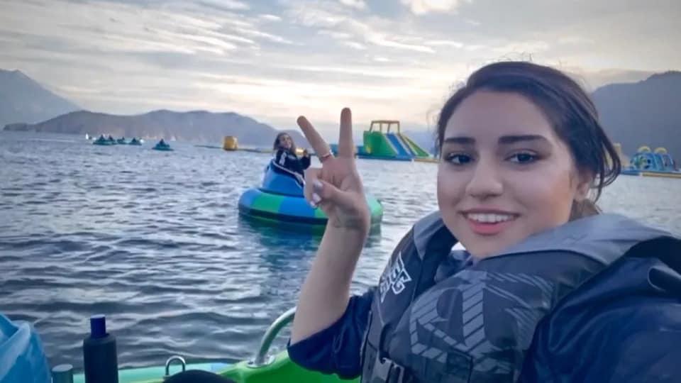 Une jeune fille se prend en photo depuis un bateau tamponneur sur un lac.