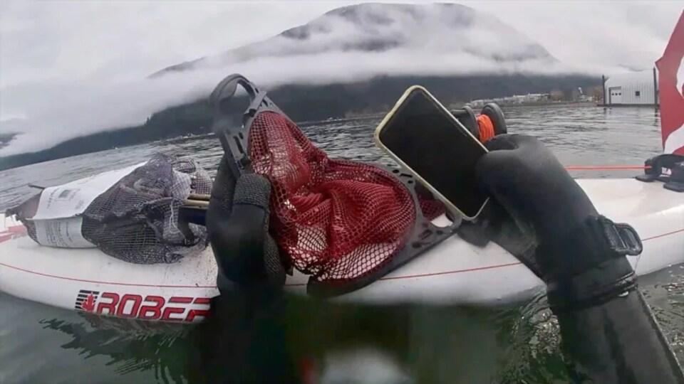 Un plongeur sort de l'eau un téléphone.