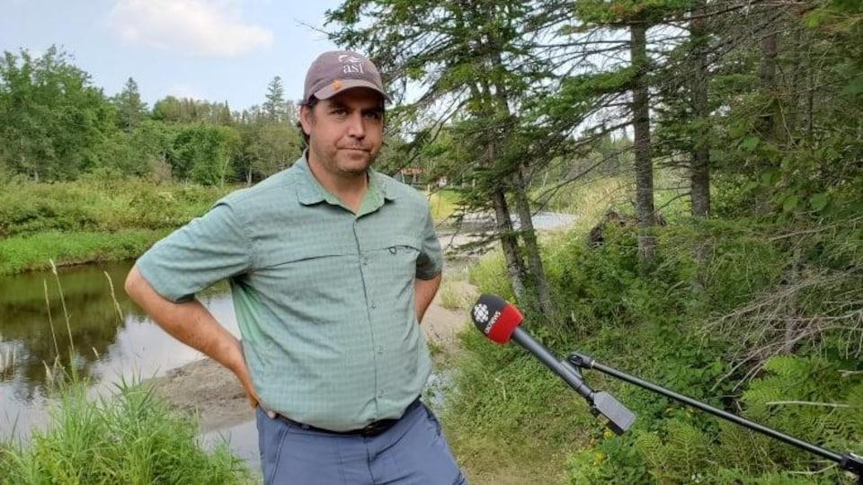 Neville Crabbe, porte-parole du Groupe de travail sur l'éradication de l'achigan à petite bouche dans la région de Miramichi, se tient debout devant un lac.