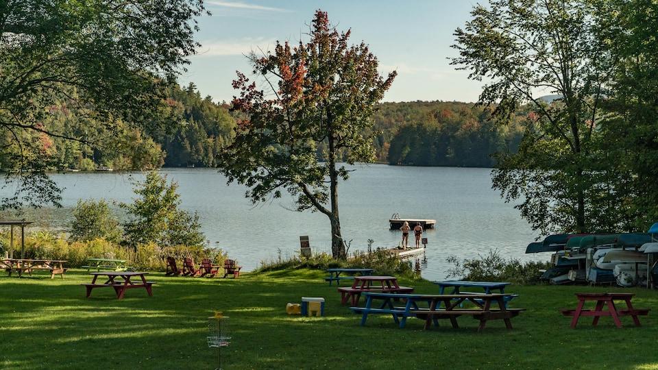 En avant-plan, des tables de pique-nique. Plus loin, deux femmes en maillot de bain sont debout sur un quai et regardent le lac.
