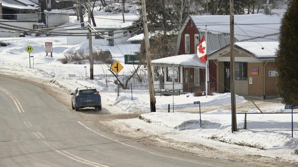 Une route passe au coeur d'un petit village enneigé.