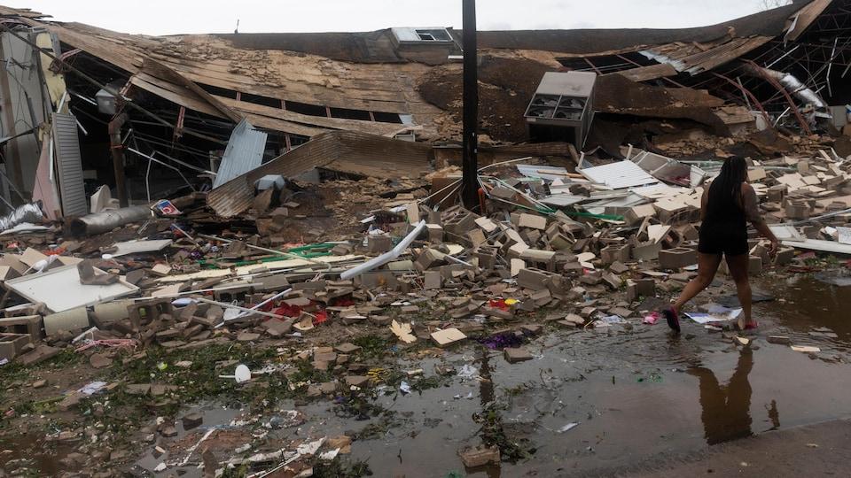 Une femme marche près d'un immeuble qui s'est effondré. Il y a des débris partout au sol.