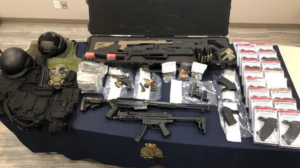 Plusieurs armes à feu sur une table.
