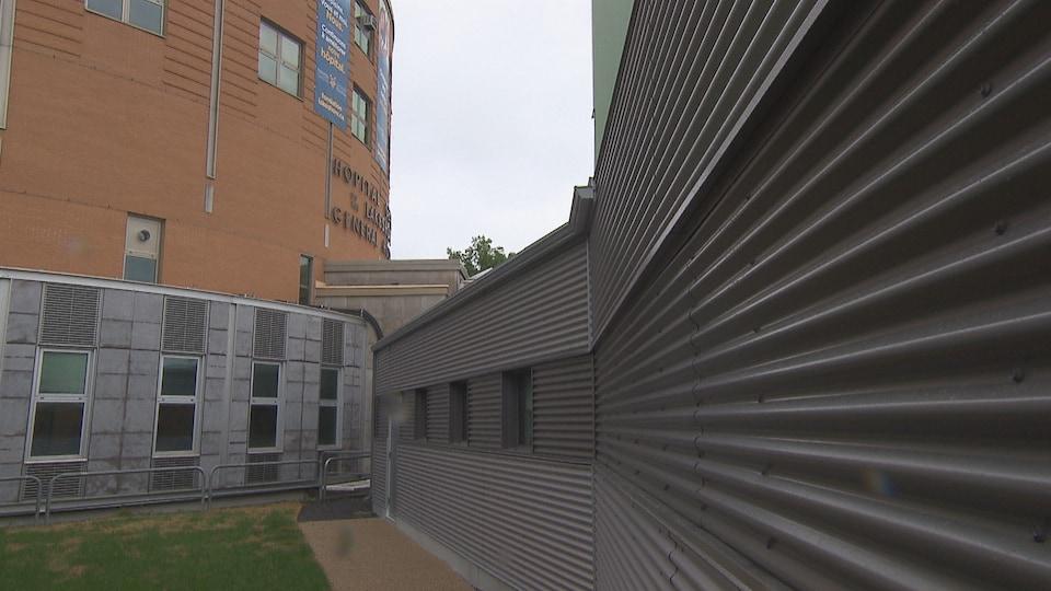 Un bâtiment en métal est rattaché au bâtiment en briques.