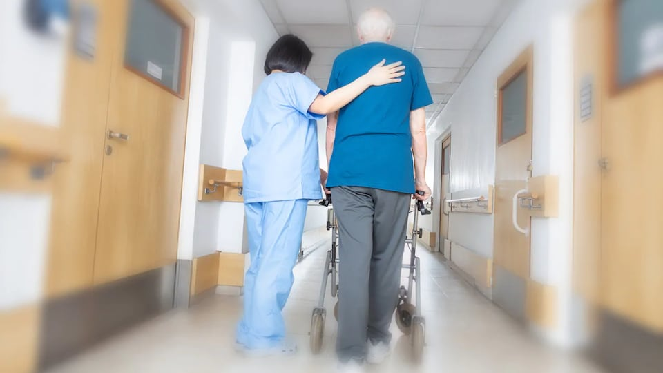 Une infirmière aide un homme à marcher dans le couloir d'un centre de soins.