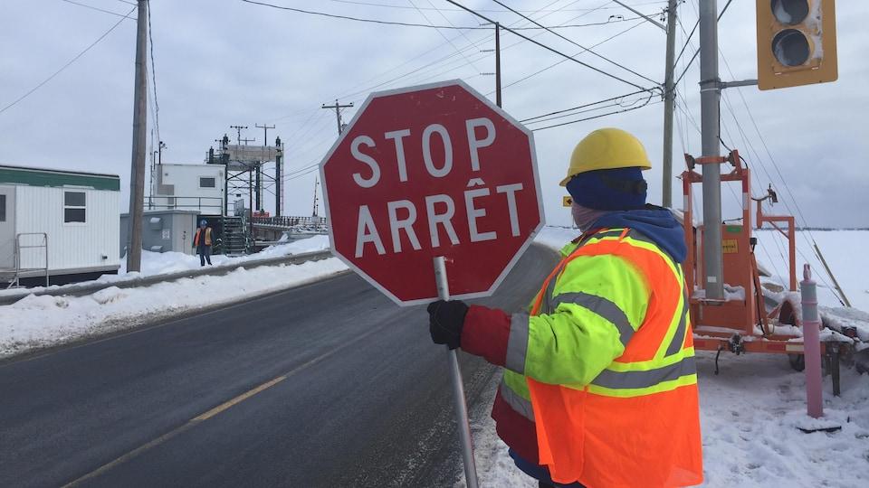 Un travailleur à l'entrée du pont tient un panneau d'arrêt.