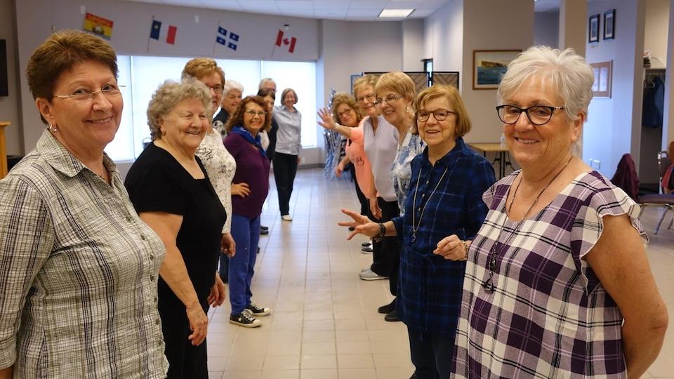 Une vingtaine de femmes prennent part à un cours de danse en ligne.