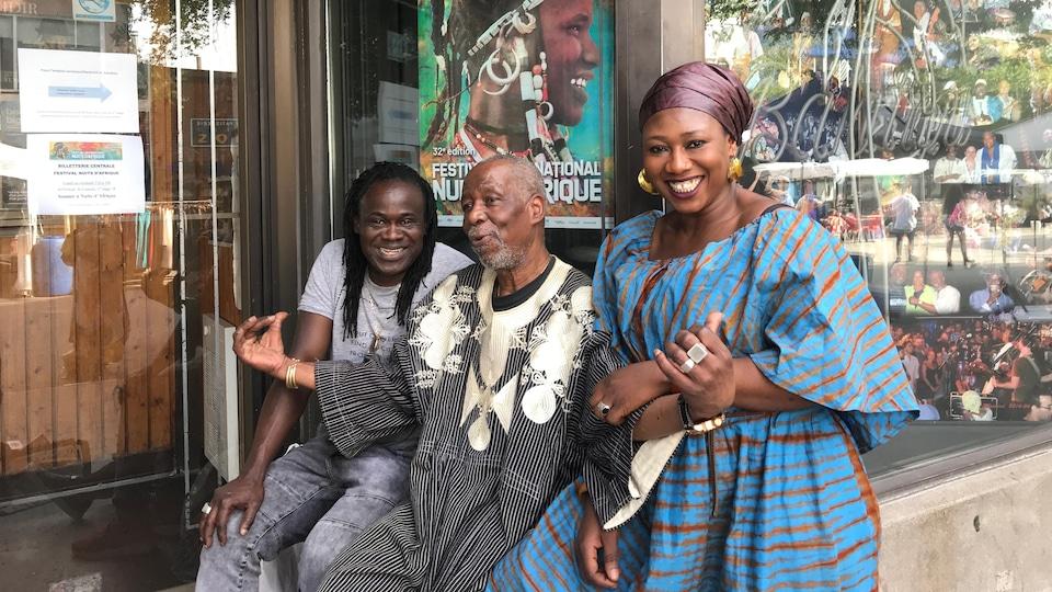 Lamine Touré, assis sur le rebord de la fenêtre à l'extérieur d'un local, parle et est flanqué d'un homme et d'une femme souriant à la caméra.