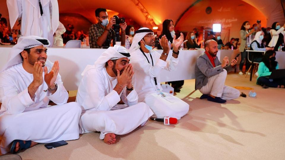 Des Émiratis souriants qui regardent le lancement applaudissent.