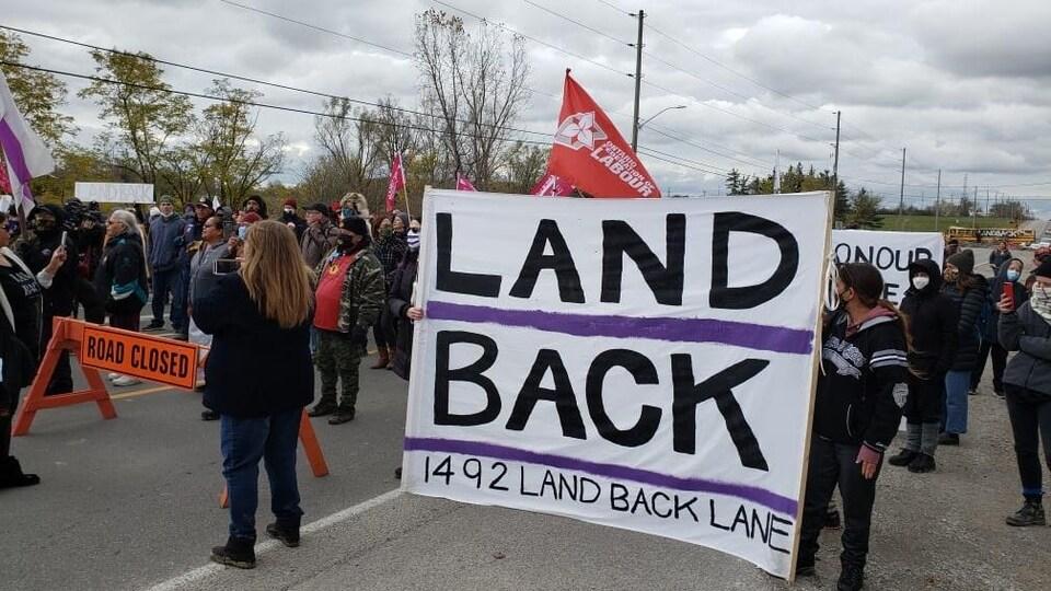 Des manifestants tiennent une pancarte.