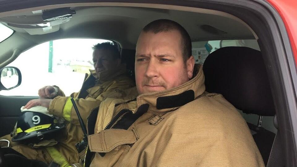 Michel Landry assis au volant d'un camion de la brigade de Grande-Anse.