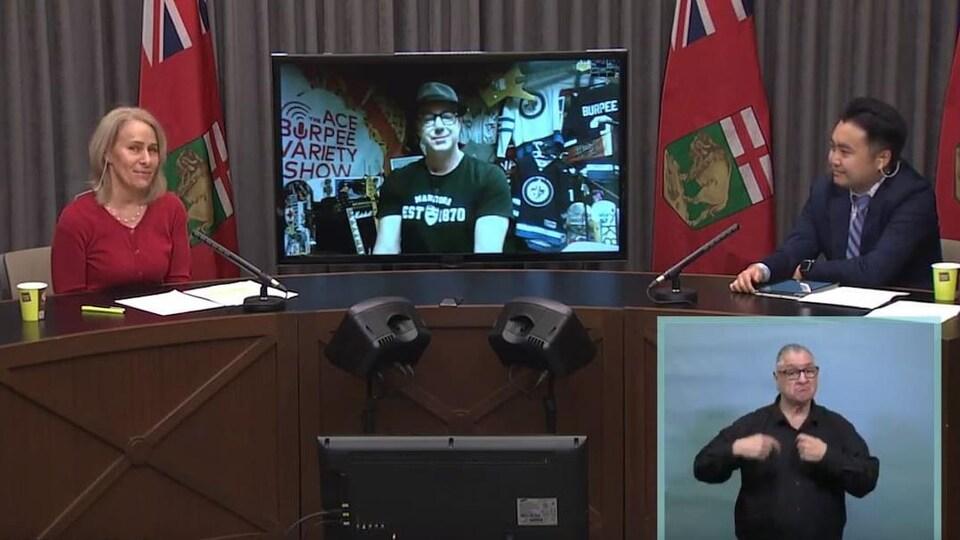 Lanette Siragusa, William Li sont dans la même salle à la même table, avec entre eux un écran sur lequel on peut voir Ace Burpee. Dans un coin de la vidéoconférence, on peut aussi voir un interprète qui signe pour les non voyants.