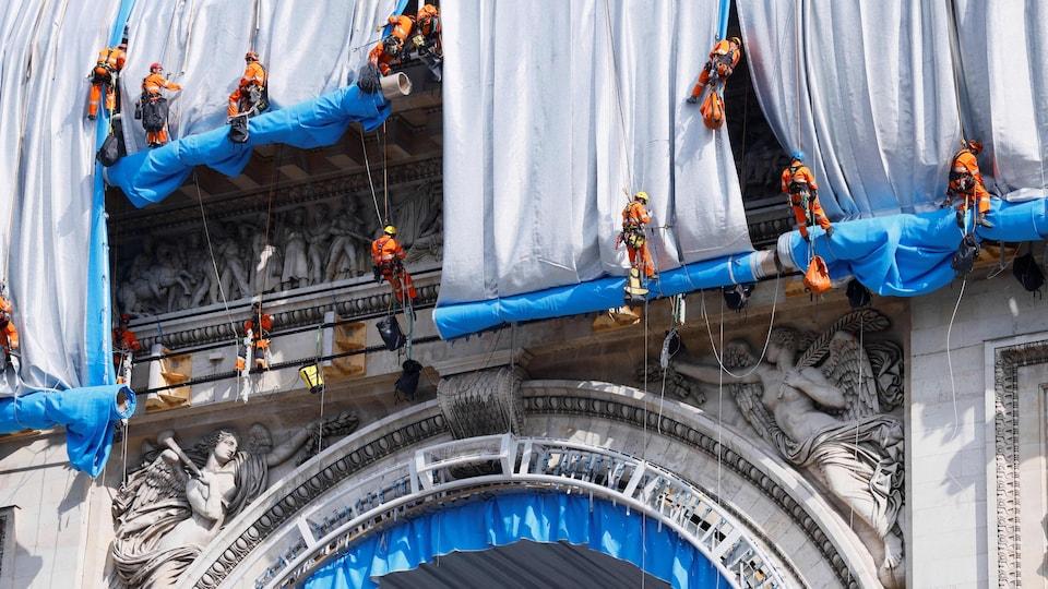 Des ouvriers suspendus à l'aide de cordes enveloppent de tissu l'Arc de Triomphe.