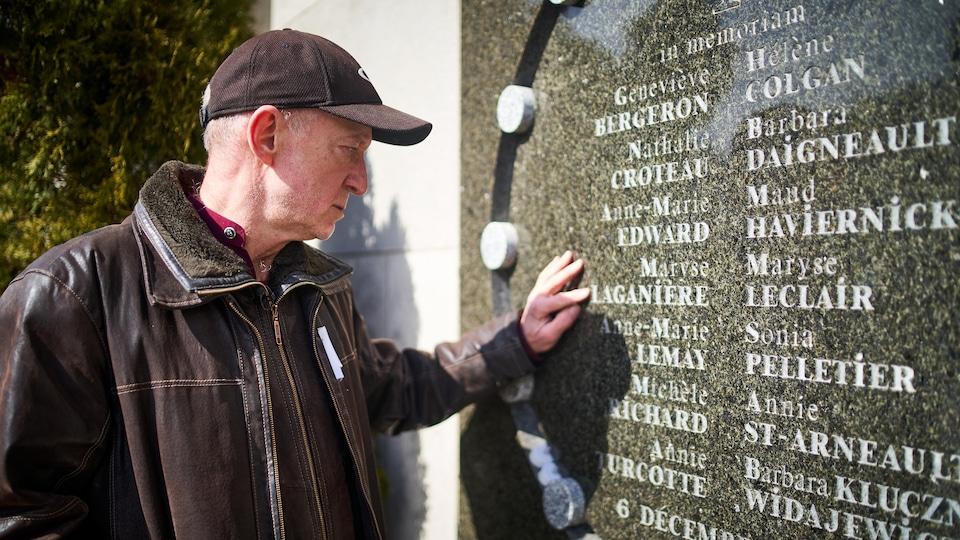 Jean-François Larivée regarde une plaque commémorative où apparaissent les noms des victimes de Polytechnique.