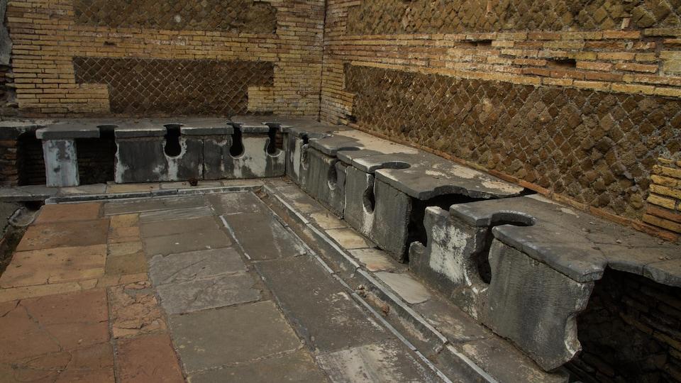 D'anciennes latrines remontant à l'Antiquité, formées de bancs qui comportent plusieurs trous, dans un site archéologique de Rome.