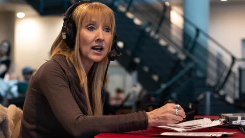 Laura-Lynn Thompson parle au micro de l'émission de radio de CBC assise devant une table rouge.