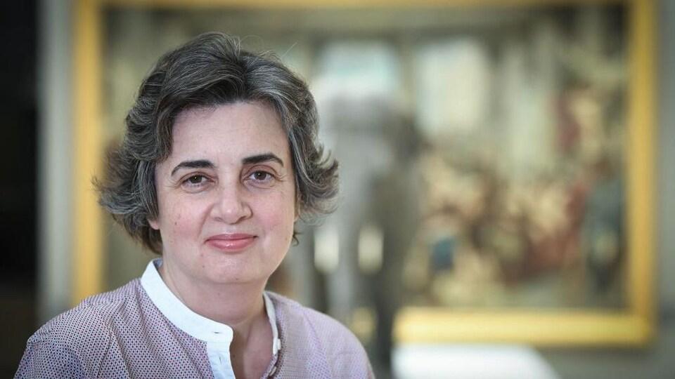 Portrait d'une femme qui esquisse un demi-sourire.