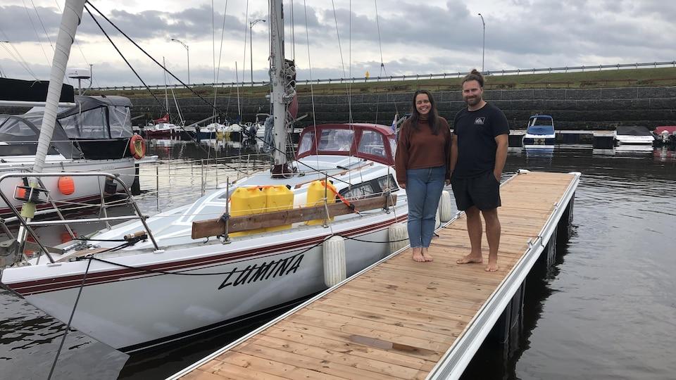 Un couple pose devant un voilier dans une marina.