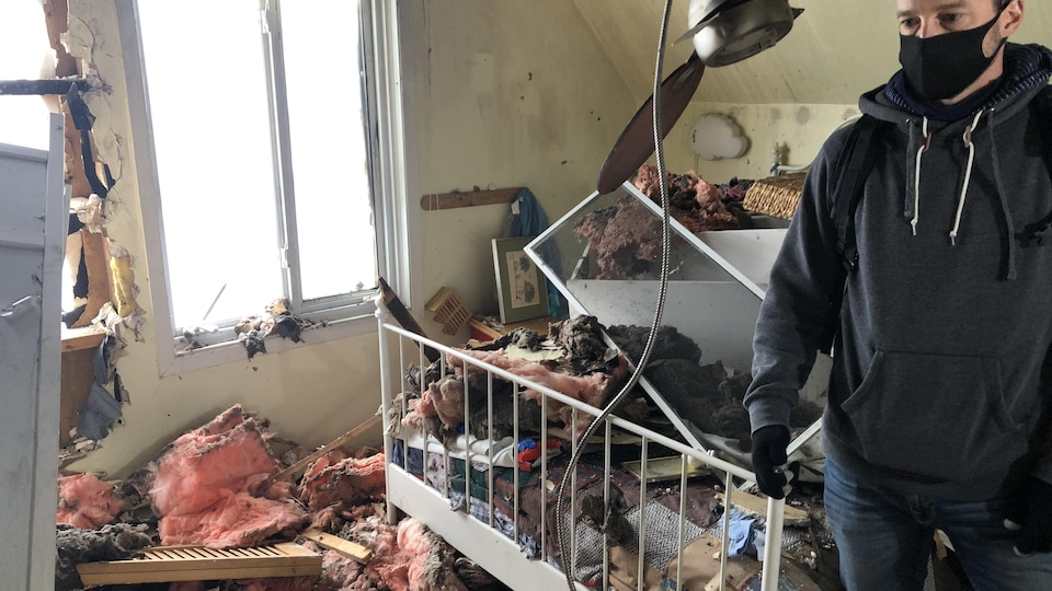 Un homme portant un masque, dans une chambre d'enfant incendiée.
