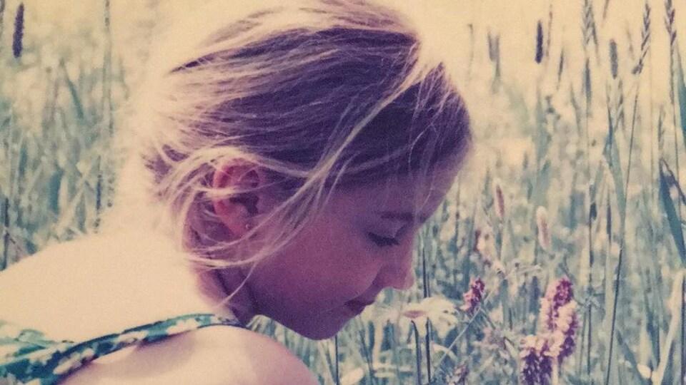 La petite Lauriane St-Jacques, à six ans, se trouve dans un champ en train de renifler des fleurs.