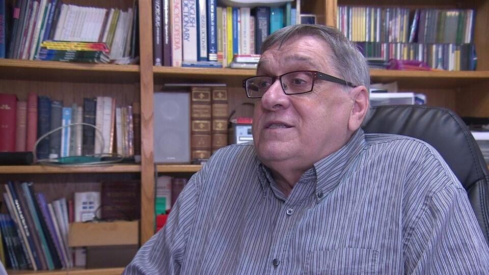 L'auteur fransaskois Laurier Gareau est assis dans son bureau avec une bibliothèque à l'arrière de lui. (archives).