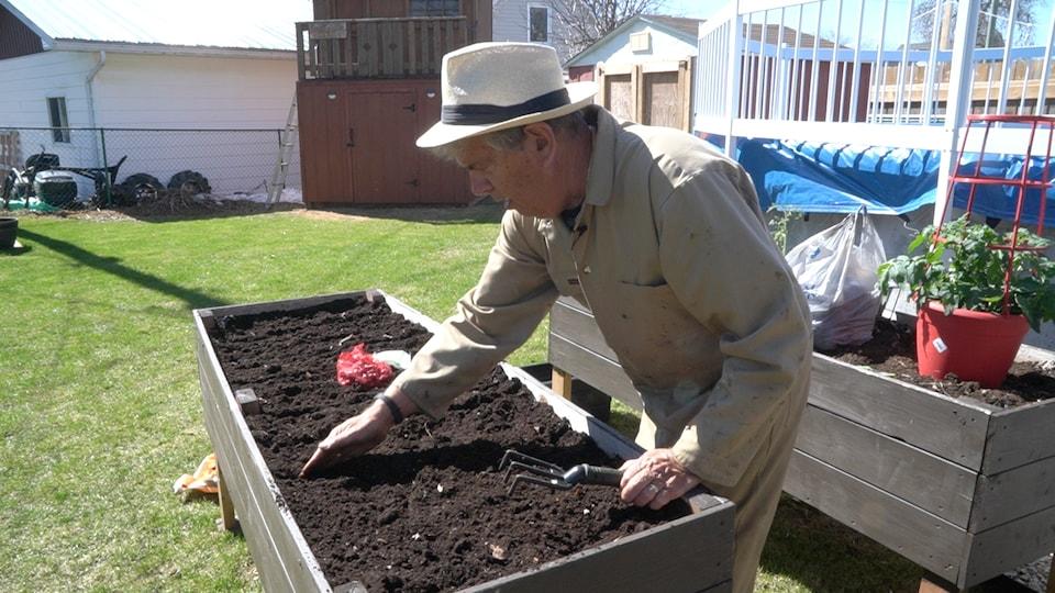 Un homme fait des sillions dans son jardin.