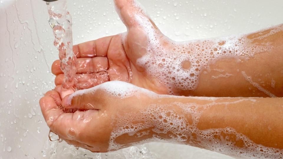 Les mains savonneuses d'un enfant sous l'eau d'un évier.
