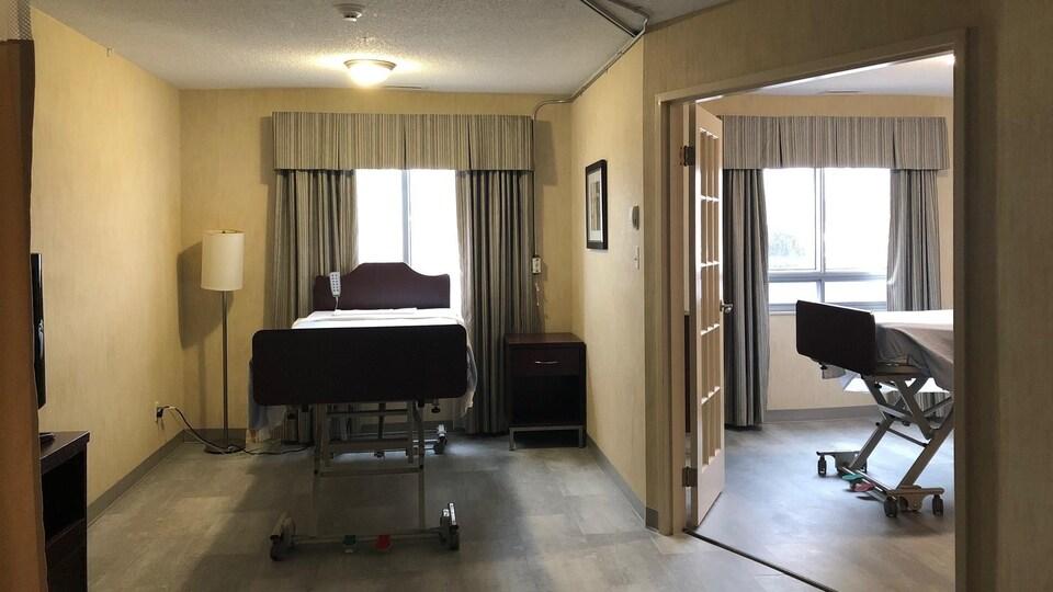Deux lits d'hôpital sont installés dans une suite d'hôtel où les deux chambres sont séparées par une double porte vitrée.