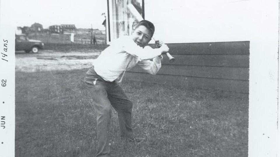 Un jeune homme de 14 ans se prépare à frapper une balle de baseball.