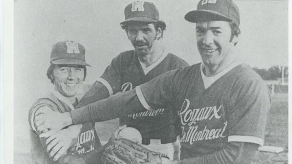 Trois hommes habillés en vêtements de baseball sourient en regardant la caméra. Ils tiennent une balle de baseball.