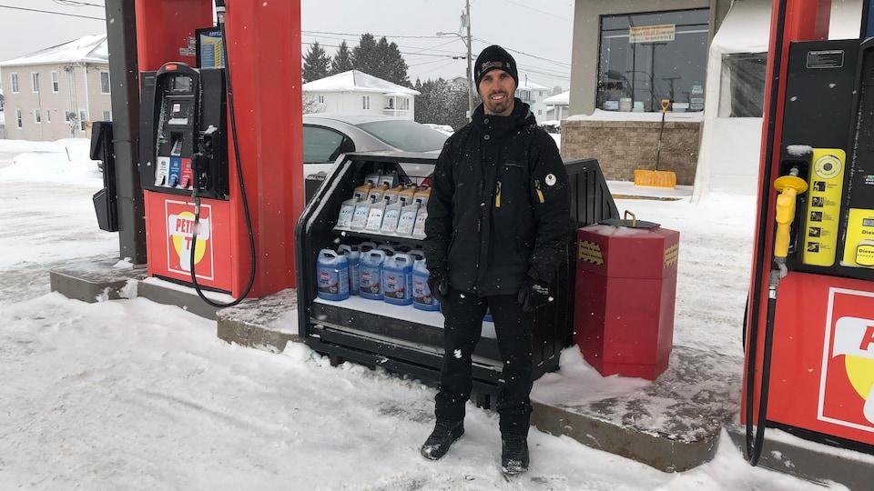 Benoît Poiraudeau devant des bidons de lave-glace dans une station service.