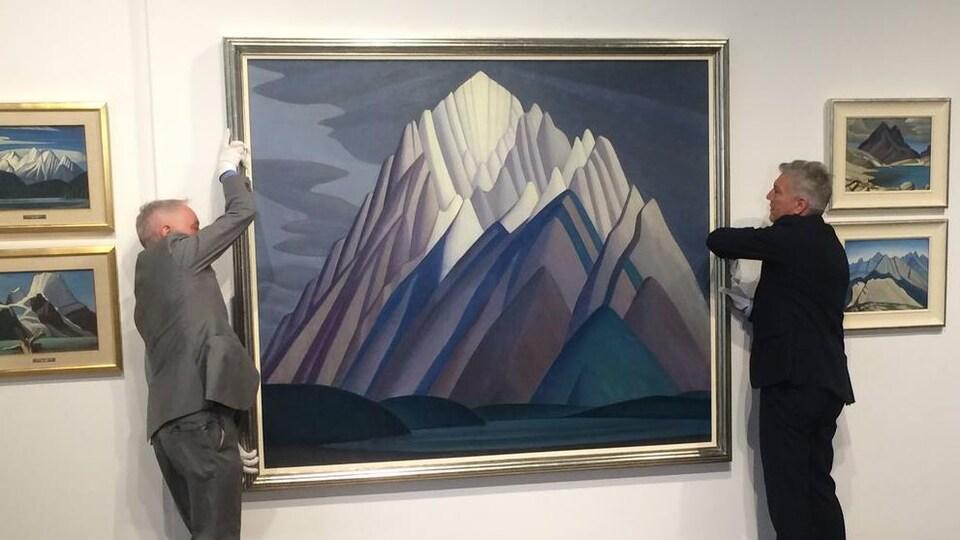 Un tableau est décroché du mur par deux vendeurs d'arts afin d'être présentée lors de la vente aux enchères.