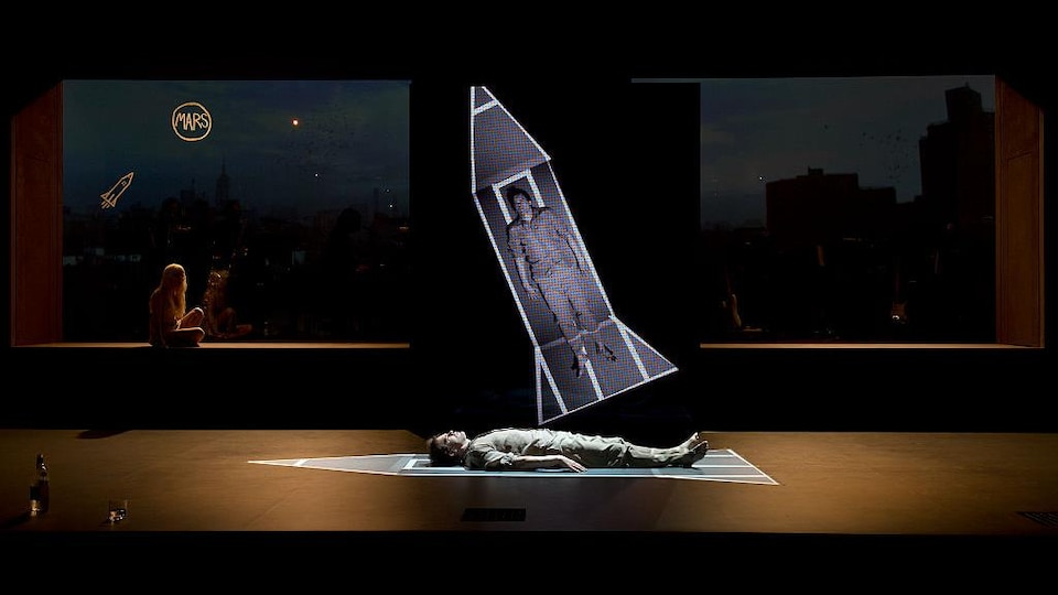 Un homme est allongé sur scène dans une sorte de fusée.