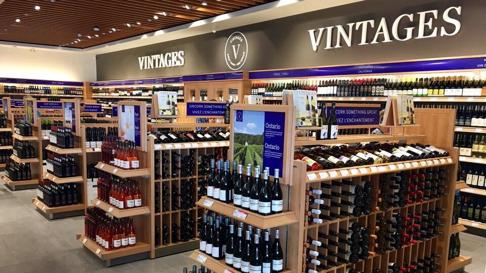 Des dizaines de bouteilles de vin se trouvent sur des tablettes dans un magasin.
