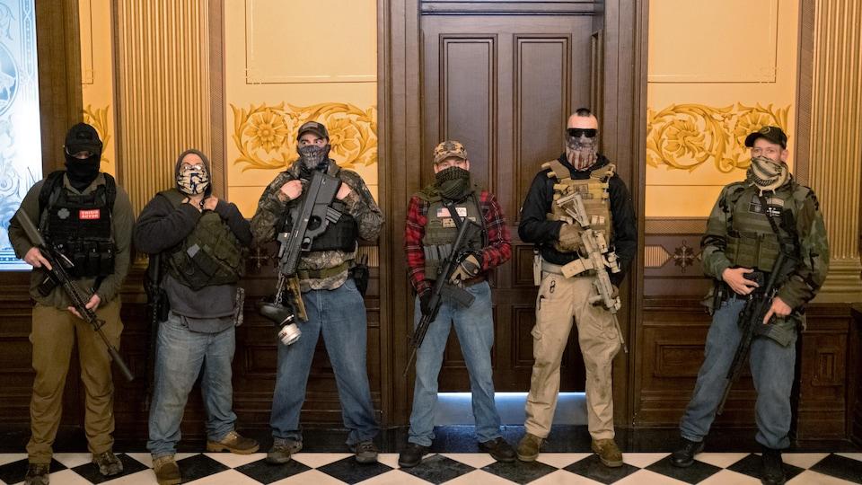 Des hommes armés et masqués à l'intérieur d'un édifice.