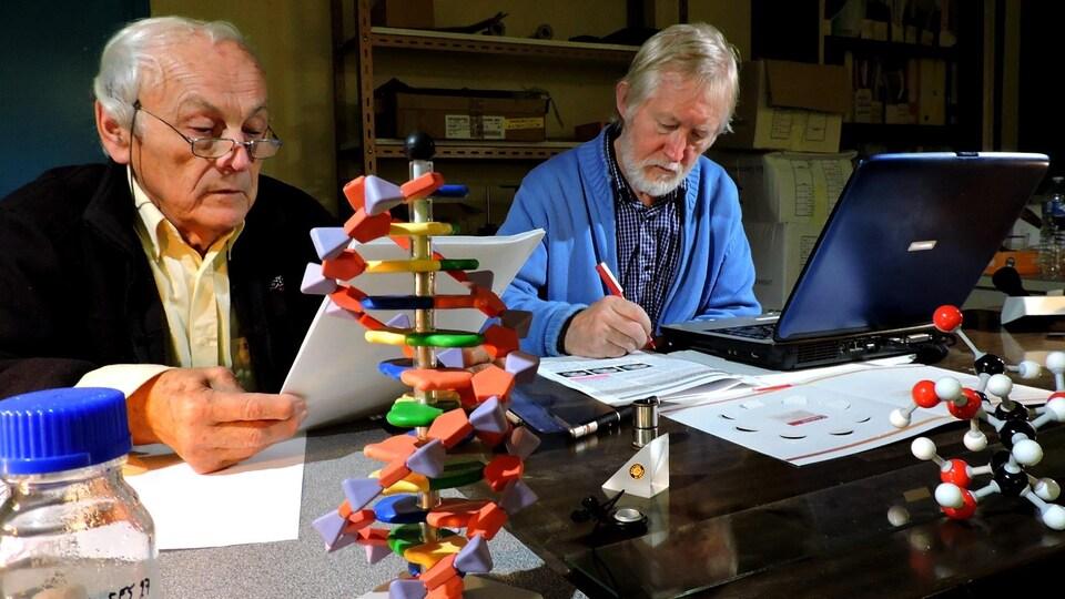 On voit les deux hommes assis, au travail, qui lisent et annotent un article scientifique.