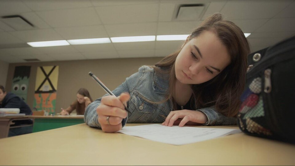 Une jeune fille répond aux questions d'un examen écrit.