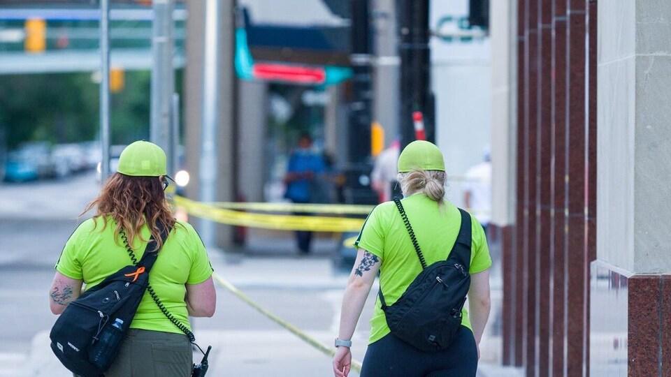 Deux femmes en T-shirt et en casquette jaune fluo.