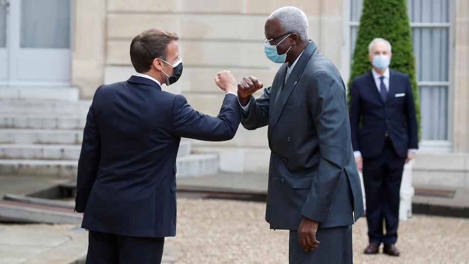 Deux hommes portant un masque se touchant le coude.