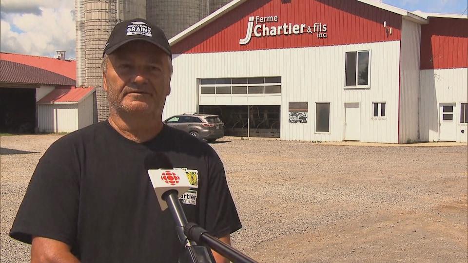 Un homme répond aux questions du journaliste devant sa ferme. Il porte une casquette.