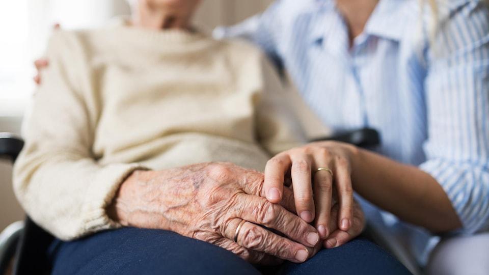 Une personne âgée est dans un fauteuil roulant et une femme lui tient la main.