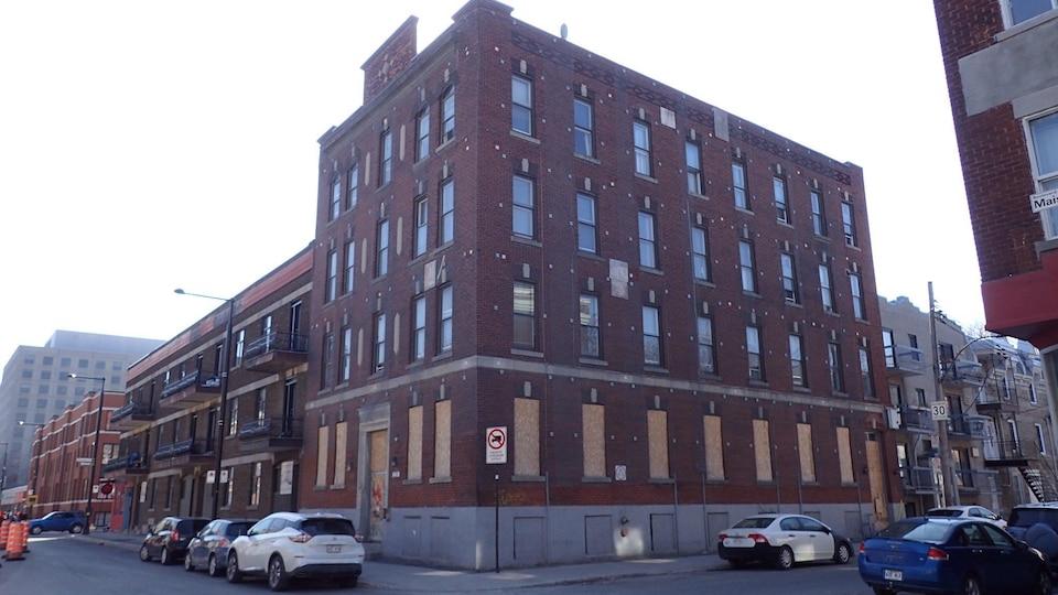 Un immeuble avec fenêtres placardées.
